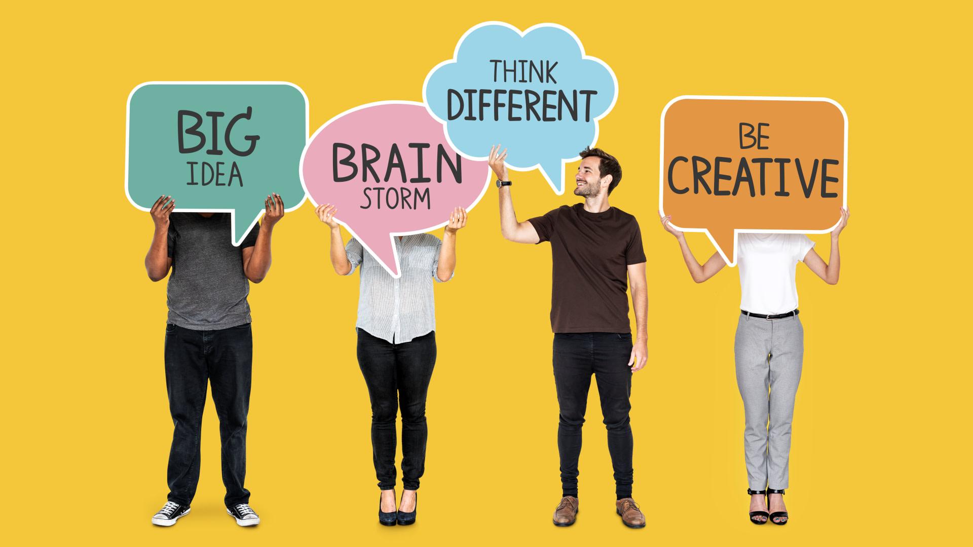 Pessoas segurando cartazes escrito Big Idea, Brain Storm Think Different e Be Creative